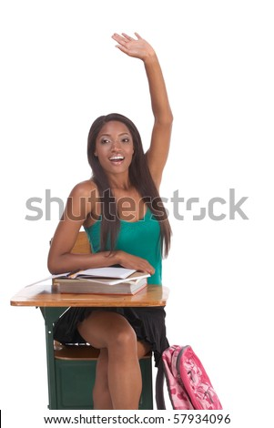 High school or college female student sitting by the desk raising her arm signaling that she know and is ready to answer and eager to participate