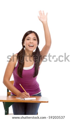 High school or college female student sitting by the desk raising her arm signaling that she know and is ready to answer - stock photo