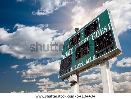 HIgh School Score Board on a Dramatic Blue Sky with Clouds and Sun Rays. - stock photo