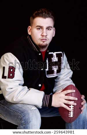 High School senior posing with football while wearing championship jacket with letter H and LB for linebacker - stock photo