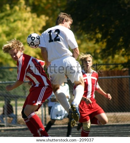 High school soccer player jumping up to bring down the ball. (editorial use only) - stock photo