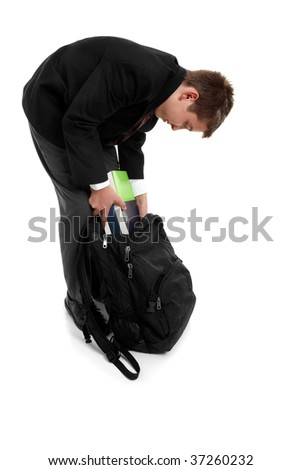 High school student placing text books in his school bag - stock photo
