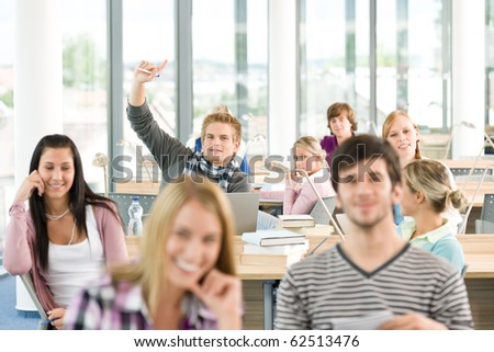 High school student raising hands in classroom - stock photo