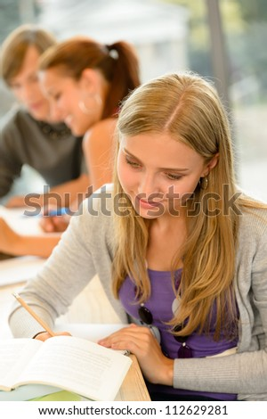 High-school student taking notes in library study academic campus teenager - stock photo