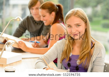 High-school student taking notes in study room smiling education campus