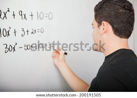 High school student writing a few math equations on a white board at school - stock photo