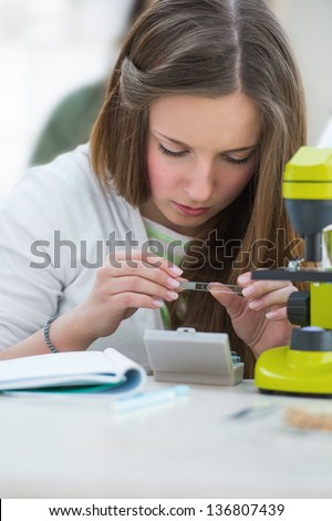 High School students. Beautiful girl working at biology classroom: holding a biological sample on glass to look through microscope - stock photo