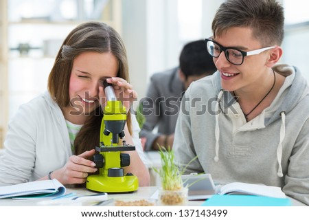 High School students. Group of excited students working in class with microscope discovering how cells looks like - stock photo