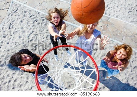 High school students playing basketball in park