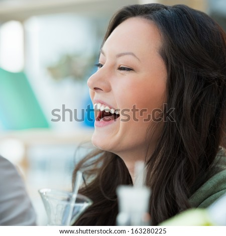 High School students. Pretty female student laughing while mixing reagents using glassware in classroom environment - stock photo