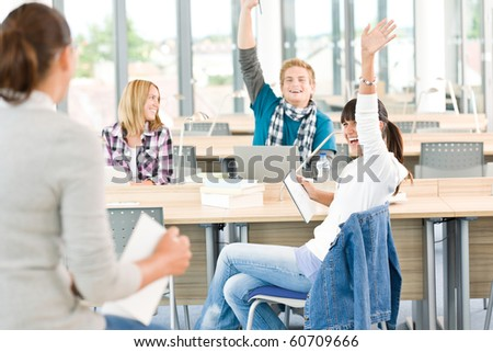 High school students raising hands, in classroom with professor - stock photo