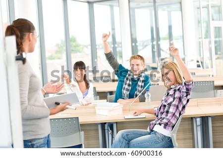 High school students raising hands, in classroom with professor - stock photo