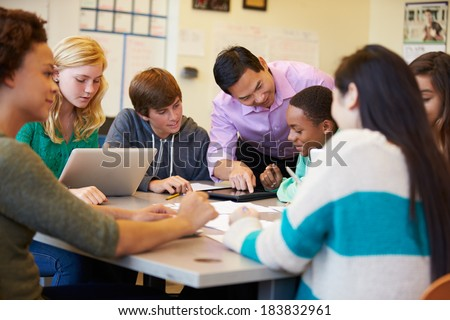 High School Students With Teacher In Class Using Laptops - stock photo