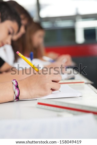High school students writing at desk in classroom