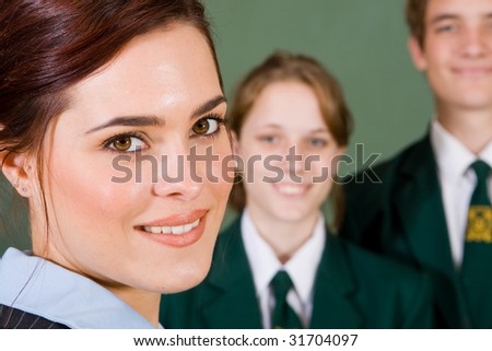 high school teacher and her students in classroom - stock photo