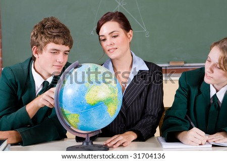 high school teacher and students viewing globe in geography classroom