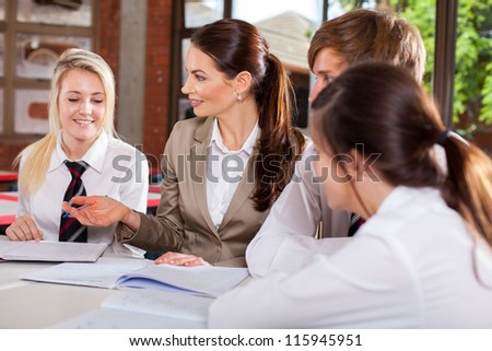 high school teacher interacting with students in classroom - stock photo