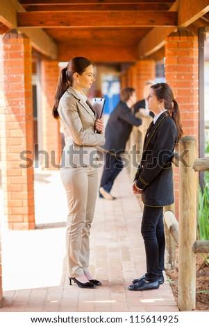 high school teacher talking to student by school corridor - stock photo