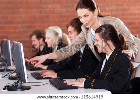 high school teacher teaching in computer room - stock photo