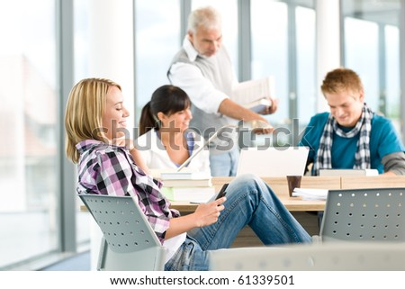 High school - three students with mature professor in classroom - stock photo