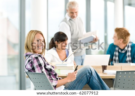 High school - three students with mature professor in classroom