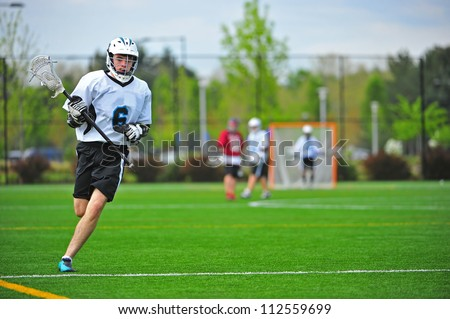 High school varsity boys lacrosse player in his protective gear on the move down the field while playing a game - stock photo