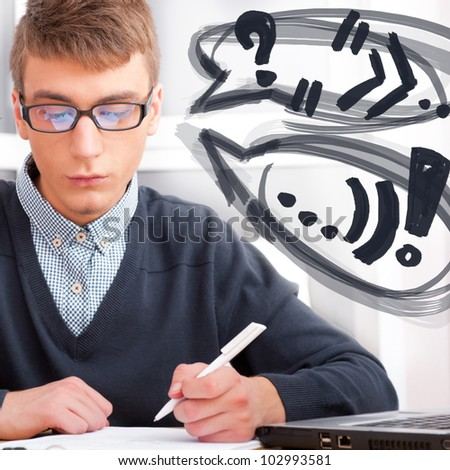 High school - Young male student write notes in classroom. Design balloons with his thoughts around his head - stock photo