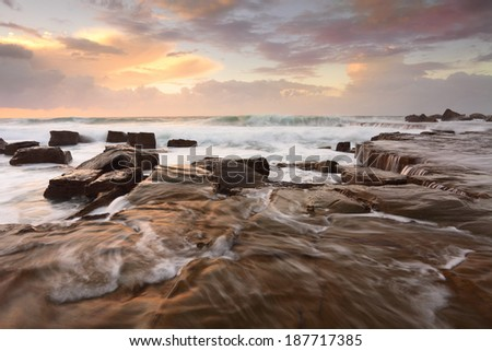 High seas, ocean waves and overflows on the rock shelf at  Forresters Beach NSW Australia - stock photo