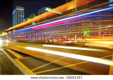 High speed and blurred bus light trails in downtown night-scape - stock photo