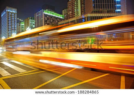 High speed and blurred bus light trails in downtown nightscape - stock photo