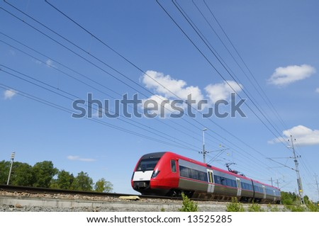 high-speed commuter train in country-side, blue sky.