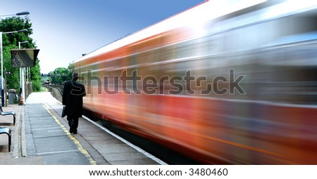 High speed commuter train passing by a railway station early in the morning. - stock photo