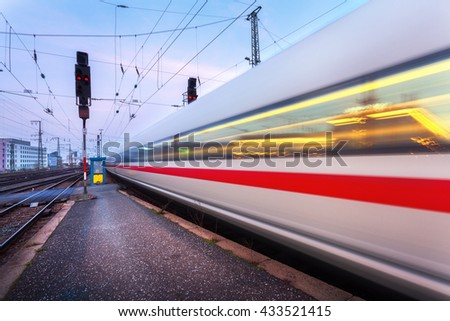 High speed passenger train on railroad track in motion at night. Blurred commuter train. Railway station in Nuremberg, Germany. Industrial landscape - stock photo