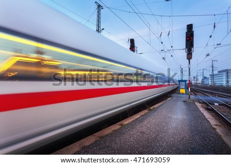 High speed passenger train on railroad track in motion at night. Blurred commuter train. Railway station at twilight in Nuremberg, Germany. Railroad travel, railway tourism. Industrial landscape