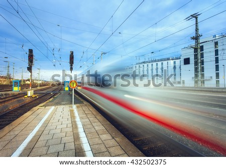 High speed passenger train on tracks in motion at sunset. Blurred commuter train. Railway station in Nuremberg, Germany. Railroad with vintage toning - stock photo