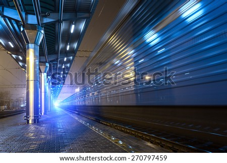 High speed passenger train on tracks with motion blur effect at night. Railway station in Ukraine