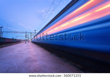 High speed passenger train on tracks with motion blur effect at sunset. Railway station in Ukraine - stock photo
