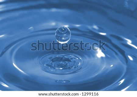 High-speed photo of a water drop frozen in time after it has impacted and rebounded a body of water.