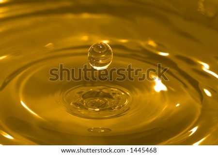 High-speed photo of a water drop frozen in time after it has impacted and rebounded a body of water. - stock photo