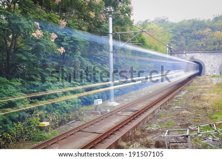 High-speed railway tunnel exit  metal rail railroad track bed light trails    - stock photo