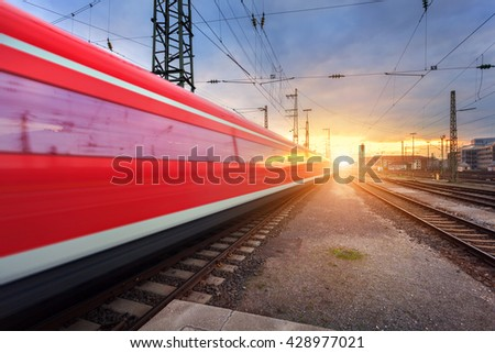 High speed red passenger train on railroad track in motion at sunset. Blurred commuter train. Railway station in Nuremberg, Germany. Industrial landscape - stock photo
