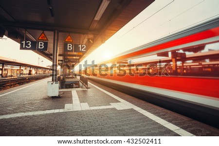 High speed red passenger train on railroad track in motion at sunset. Blurred commuter train. Railway station in Nuremberg, Germany. Industrial landscape with instagram toning - stock photo