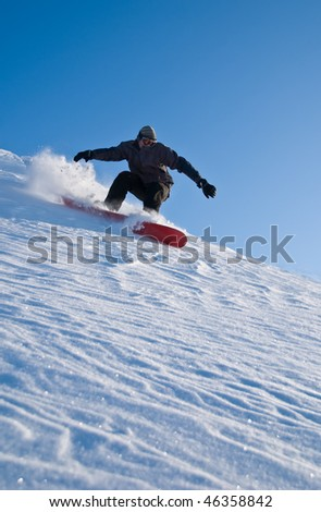 High Speed Snowboarder turning sharply in powder snow, ice crystals flying