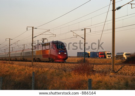 High speed TGV train in France passing by trucks on highway. - stock photo