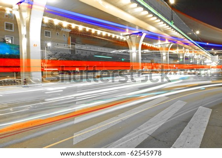 High speed traffic and blurred light trails under the overpass - stock photo