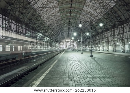 High speed train departs from the station at night time. - stock photo
