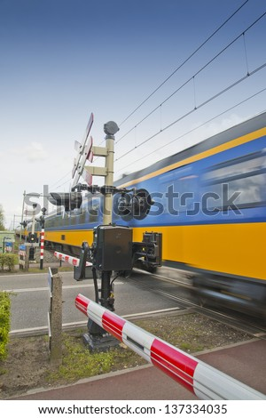high speed train passing a railroad crossing in the Netherlands - stock photo