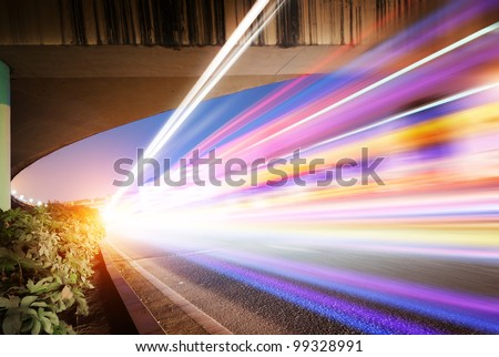 High-speed vehicles bright light trails on urban roads under the overpass at night - stock photo