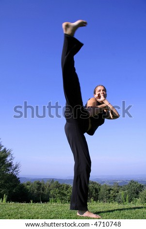 high split kick - attractive young woman practicing self defense