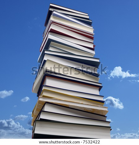 high stack of books in front of a blue sky - stock photo